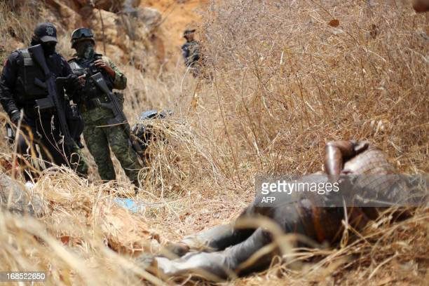 Soldiers observe a corpse found burnt and with signs of torture in Acapulco's Mozimba neigbourhood Guerrero State Mexico on May 10 2013 Guerrero home...