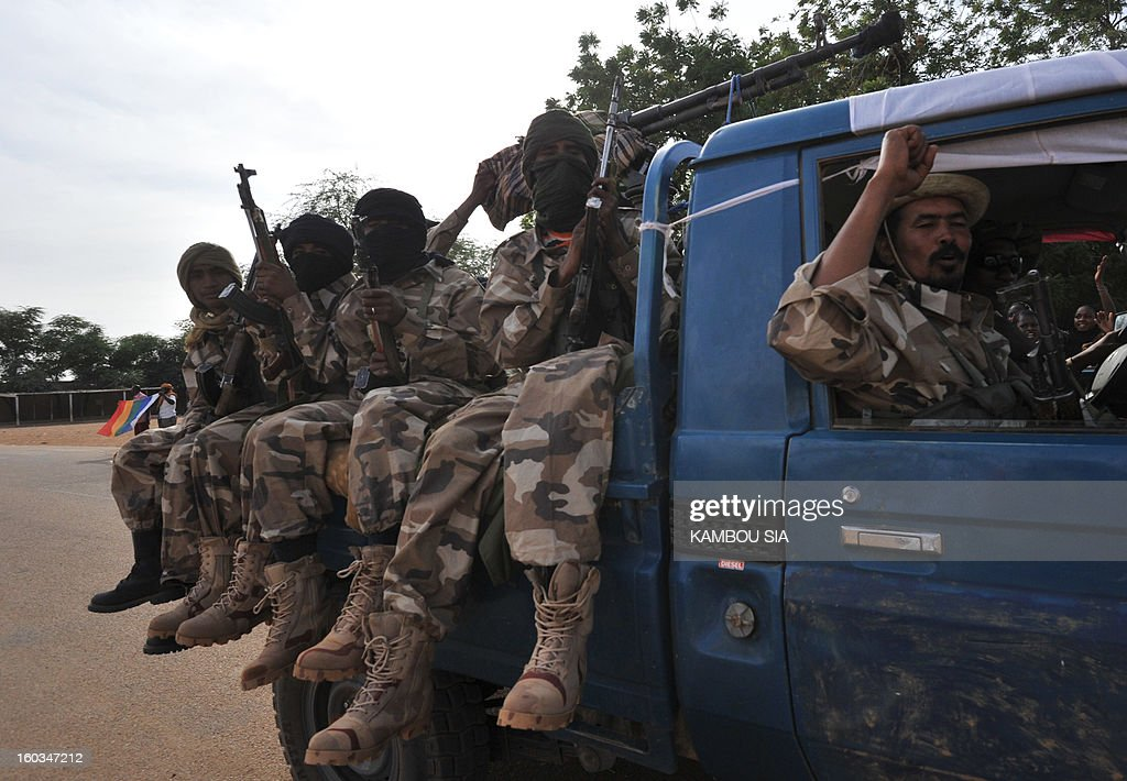 Soldiers of Malian Colonel Alaji Ag Gamou sit on a pick-up truck as they enter on January 29, 2013 Ansongo, a town south of the northern Malian city of Gao. Troops from Niger and Mali on January 29 entered Ansongo, which along with Gao was recaptured by French-led soldiers over the weekend in a lightning offensive against radicals holding Mali's north. So far, just 2,000 African troops have been sent to Mali or neighboring Niger, many of them from Chad, to boost the French-led offensive which began on January 11 and led to the recapture of several towns, including Ansongo.