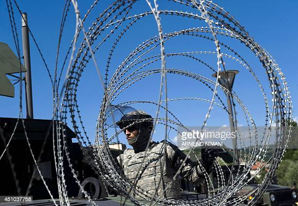 US soldiers of NATOled peacekeepers in Kosovo install razor wire on the main bridge during clashes with protesters on June 22 2014 in the divided...