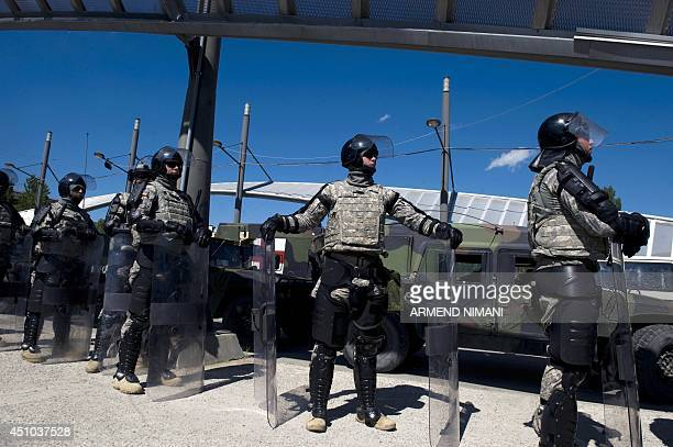 US soldiers of NATOled peacekeepers in Kosovo stand guard on the main bridge during clashes with protesters on June 22 2014 in the divided town of...