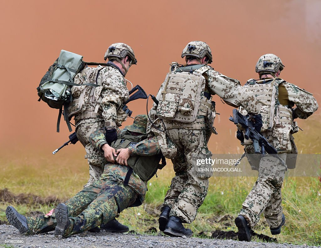 Soldiers of the 33rd Panzergrenadier bataillon evacuate a wounded comrade during a drill at the headquarters of the 33rd Panzergrenadier bataillon in Neustadt am Ruebenberge on June 29, 2016. / AFP / JOHN