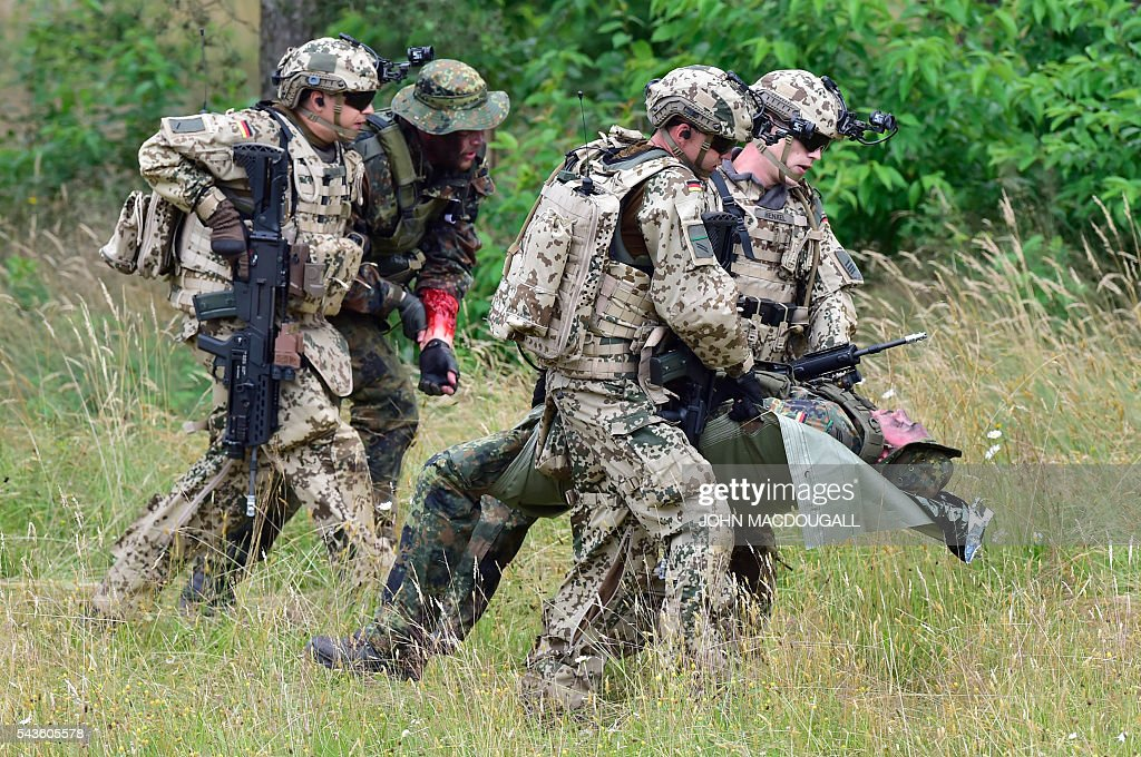 Soldiers of the 33rd Panzergrenadier bataillon evacuate wounded comrades during a drill at the headquarters of the 33rd Panzergrenadier bataillon in Neustadt am Ruebenberge on June 29, 2016. / AFP / JOHN