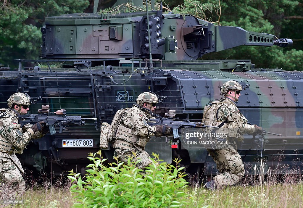 Soldiers of the 33rd Panzergrenadier bataillon run past a Puma armoured infantry fighting vehicle during a drill at the headquarters of the 33rd Panzergrenadier bataillon in Neustadt am Ruebenberge on June 29, 2016. / AFP / JOHN