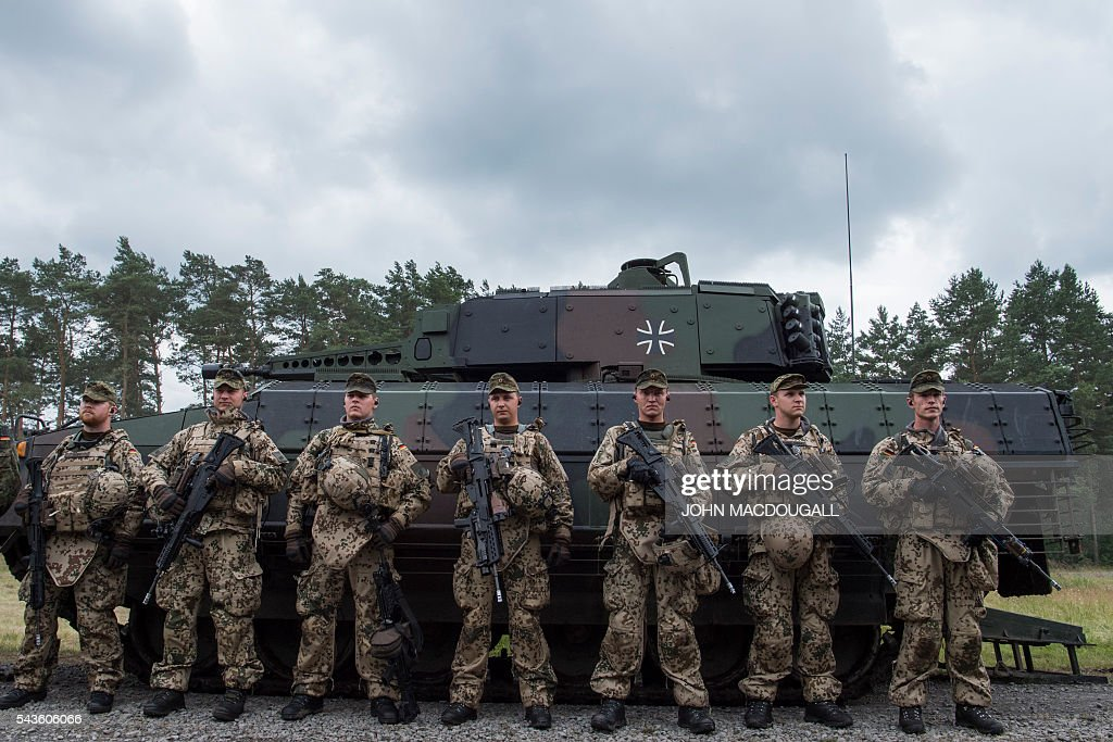 Soldiers of the 33rd Panzergrenadier bataillon stand ready for inspection in front of a Puma infantry fighting vehicle after taking part in a drill at the headquarters of the 33rd Panzergrenadier bataillon in Neustadt am Ruebenberge on June 29, 2016. / AFP / JOHN