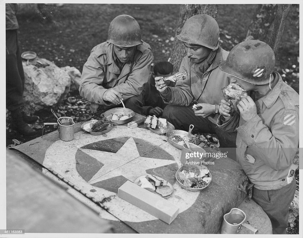 US soldiers of the 3rd Division having Christmas dinner on the hood of a jeep on the front lines, World War Two, France, December 25th 1943.