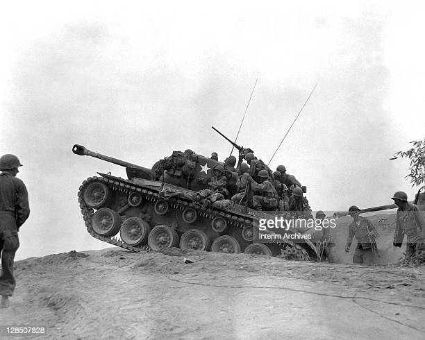 Soldiers of the 9th Infantry Regiment gather upon the rear of a M26 Pershing tank as they await an enemy attempt to cross the Naktong River during...