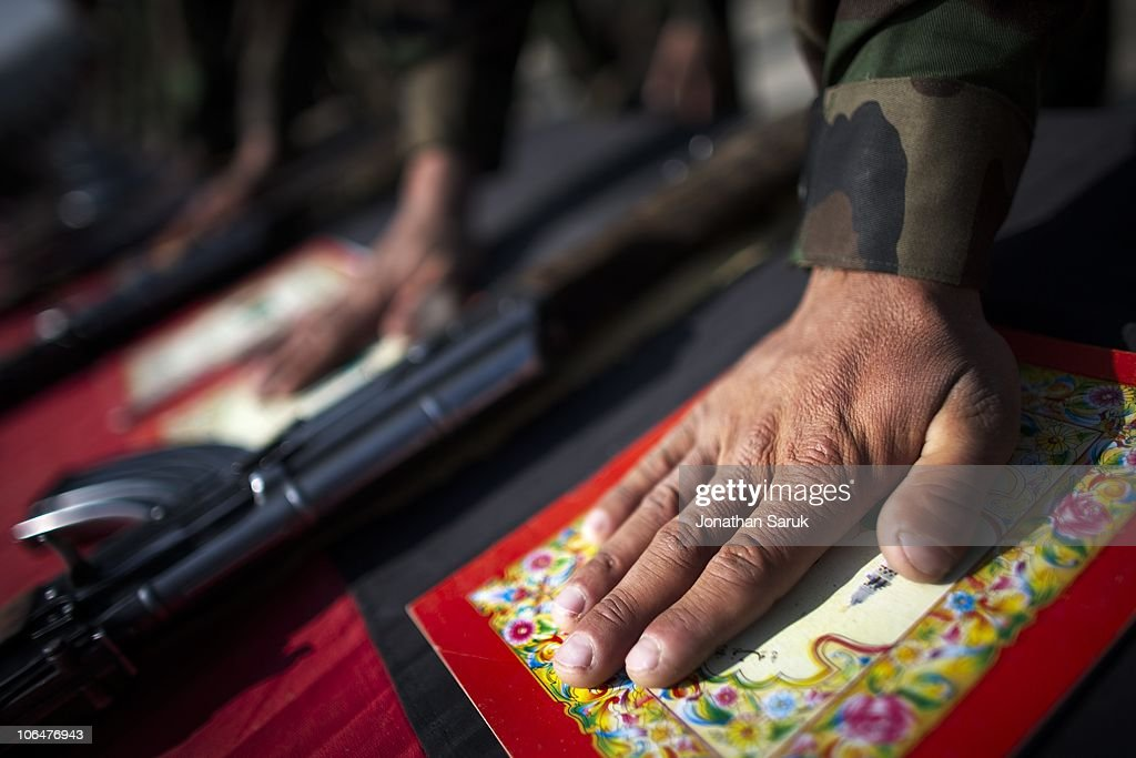 Soldiers of the Afghanistan National Army take an oath to defend their country by placing their hand on a booklet of excerpts from the Koran during a mid-course ceremony at the Kabul Military Training Center March 19, 2009 in Kabul, Afghanistan. A group of 1,200 soldiers have completed five weeks of training of a ten week course. Approximately 25,000 soldiers a year graduate from the program located on the outskirts of Kabul. Increasing the number of Afghan soldiers is a major goal of coalition forces in Afghanistan.