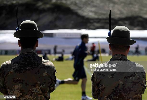 Soldiers of the Alpini the Italian mountain military corps watch members of Italy's national football squad during a training session in Sestriere on...