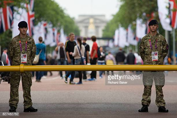 Soldiers of the British army stand guarding the entrance to the volleyball venue in central London next to the IOC rings logo on day 4 of the London...