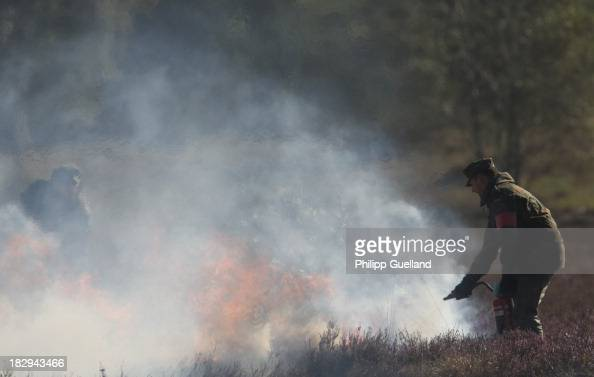 Soldiers of the Bundeswehr extinguish a bushfire caused by flares during the annual military exercises held for the media at the Bergen military...