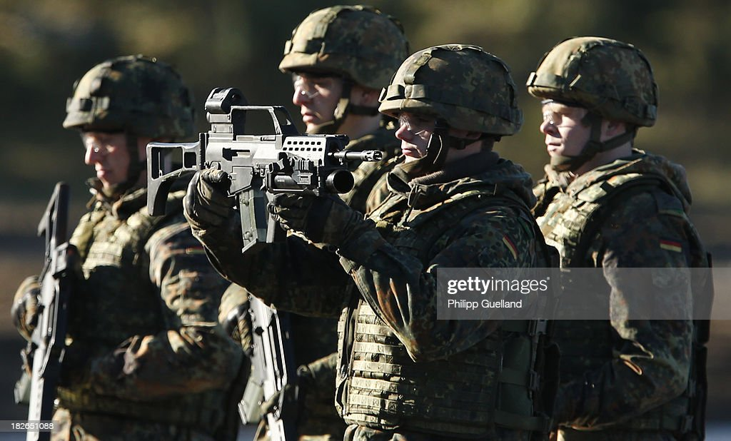 Soldiers of the Bundeswehr present their Heckler und Koch G36 assault rifles during the annual military exercises held for the media at the Bergen military training grounds on October 2, 2013 near Munster, Germany. The Bundeswehr is transitioning to a professional army as Germany recently ended mandatory military service.