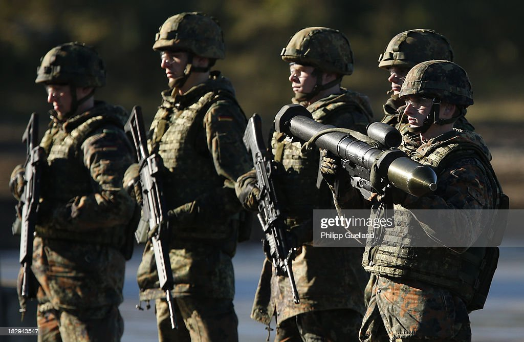 Soldiers of the Bundeswehr present their weapons during the annual military exercises held for the media at the Bergen military training grounds on October 2, 2013 near Munster, Germany. The Bundeswehr is transitioning to a professional army as Germany recently ended mandatory military service.
