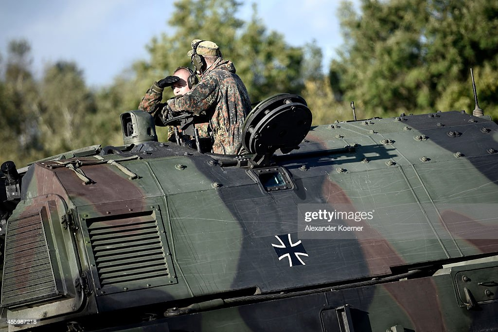 Soldiers of the Bundeswehr the German armed forces sit on top of the heavy artillery tank `Panzerhaubitze 2000` during the annual military exercises...