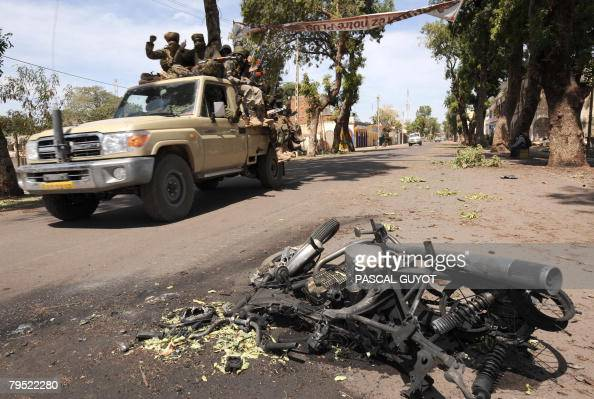 Soldiers of the Chadian army on patrol drive by a burnt motorbike downtown N'Djamena on February 5 2008 where heavy fights took place in the last...