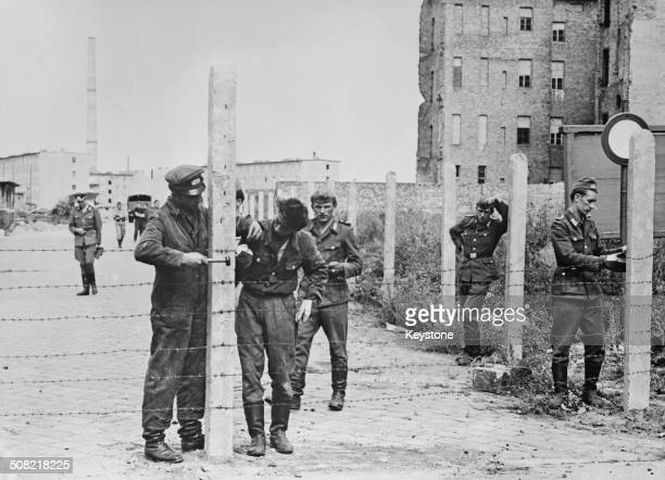 Soldiers of the East German National People's Army erecting barbed wire fences to close off a street in preparation for the construction of the...