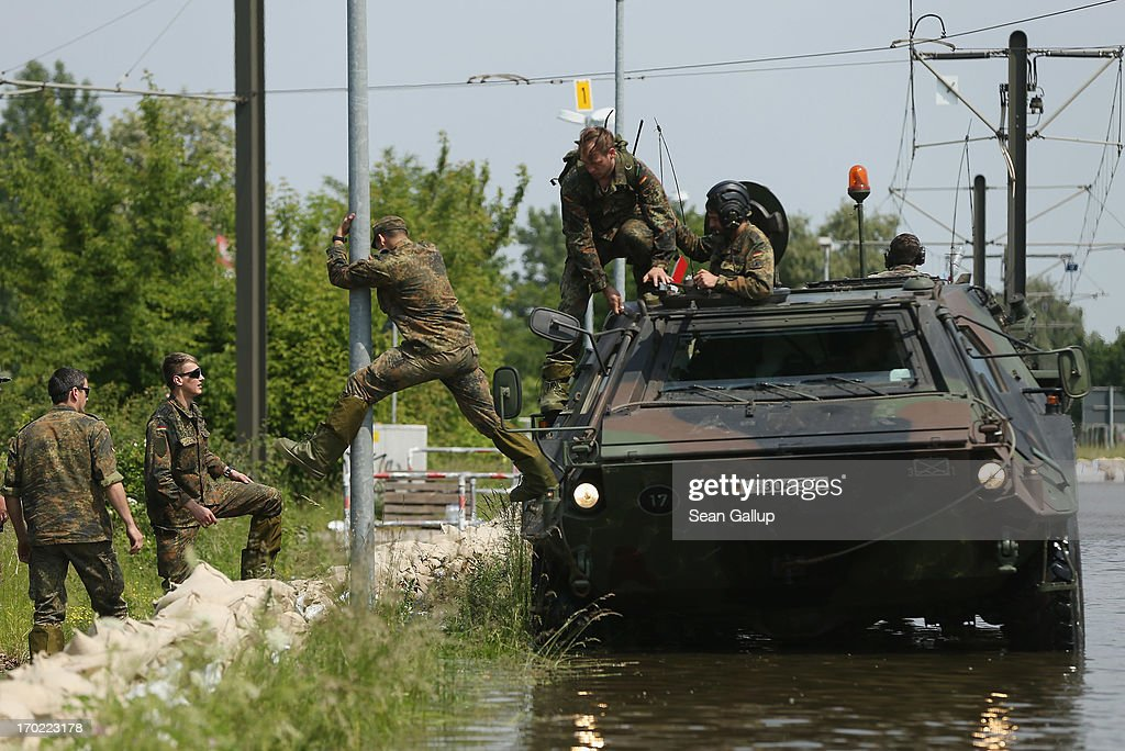 Soldiers of the German Bundeswehr descend from a TPz Fuchs amphibious transporter in floodwaters from the swollen Elbe river at an industrial park in the Rothensee district on June 9, 2013 in Magdeburg, Germany. Magdeburg is enduring its highest floodwaters in its 1,200 year history and several city districts are underwater. Catastrophic flooding has hit portions of southern and eastern Germany that has left at least seven people dead and forced tens of thousands to flee their homes. Towns in northern Germany downstream from the Elbe are also bracing for floods in coming days.
