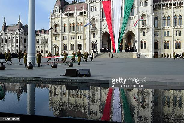 Soldiers of the Hungarian honour guard march with the national flag in front of the parliament building near the memorial of the 1956 antiSoviet...