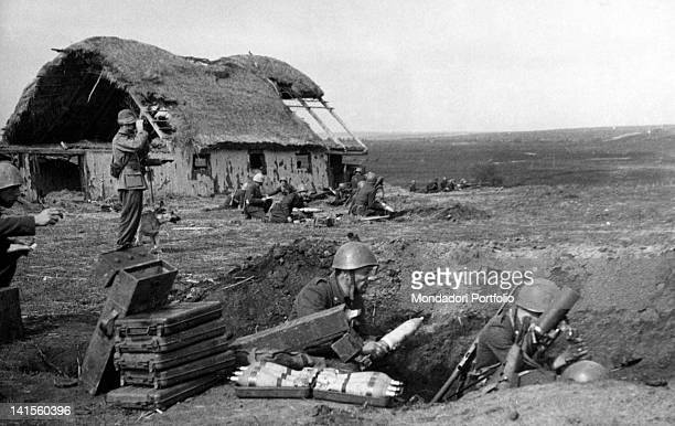 Soldiers of the Italian Alpine Troops of 'Monte Cervino''s battalion lying in wait beside the ruins of an izba ready to open fire Klinovj June 1942