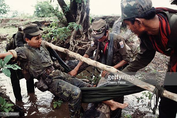 Soldiers of the Karen National Liberation Army carry a wounded comrade hit by a Burmese army bullet during an ambush operation