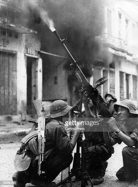 Soldiers of the National Liberation Front firing a machine gun at US aircraft during an air raid on a village in South Vietnam during the Vietnam War
