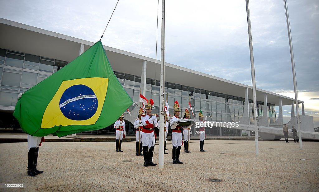 Soldiers of the presidential guard prepare to raise the flag at half-mast at the Planalto Palace in Brasilia to honor the victims of a nightclub blaze in Santa Maria, Southern of Brazil on January 28, 2013. Brazilians on Monday were mourning the victims of a nightclub blaze in a small university town that left more than 230 people dead and over 100 injured, with many still fighting for their lives. AFP PHOTO/Pedro LADEIRA