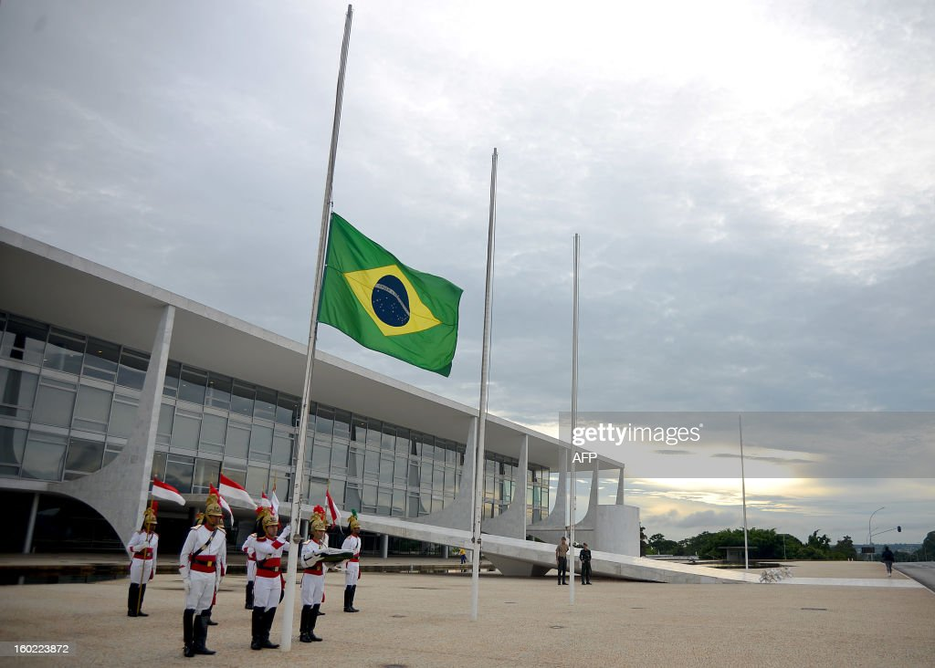 Soldiers of the presidential guard raise the flag at half-mast at the Planalto Palace in Brasilia to honor the victims of a nightclub blaze in Santa Maria, Southern of Brazil on January 28, 2013. Brazilians on Monday were mourning the victims of a nightclub blaze in a small university town that left more than 230 people dead and over 100 injured, with many still fighting for their lives. AFP PHOTO/Pedro LADEIRA