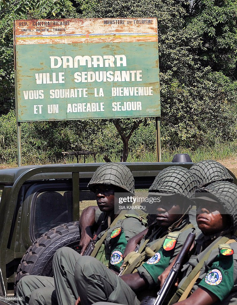 Soldiers of the regional African force FOMAC arrive in Damara, the last strategic town between the rebels from the SELEKA coalition and the country's capital Bangui, on January 2, 2013, as FOMAC commander warned rebels against trying to take the town, saying it would 'amount to a declaration of war.' The rebels, who began their campaign a month ago and have taken several key towns and cities, have accused Central African Republic leader Francois Bozize of failing to honor a 2007 peace deal. The sign reads in French 'The seductive city of Damara welcomes you and wishes you a pleasant stay.' AFP PHOTO/ SIA KAMBOU