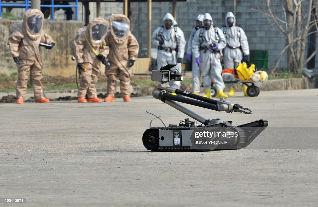Soldiers of the US Army's 23rd Chemical Battalion (background) wear protective gear to give a demonstration of their equipment as iRobot PackBot (front) moves during a ceremony to recognise their official return to the 2nd Infantry Division located in South Korea, at Camp Stanley in Uijeongbu, north of Seoul, on April 4, 2013. The 23rd Chemical Battalion left South Korea in 2004 but the battalion with about 250 soldiers returned to the South in January 2013. The battalion will provide nuclear, biological and chemical detection, equipment decontamination and consequence management assistance to support the US and South Korean military forces. AFP PHOTO / JUNG YEON-JE