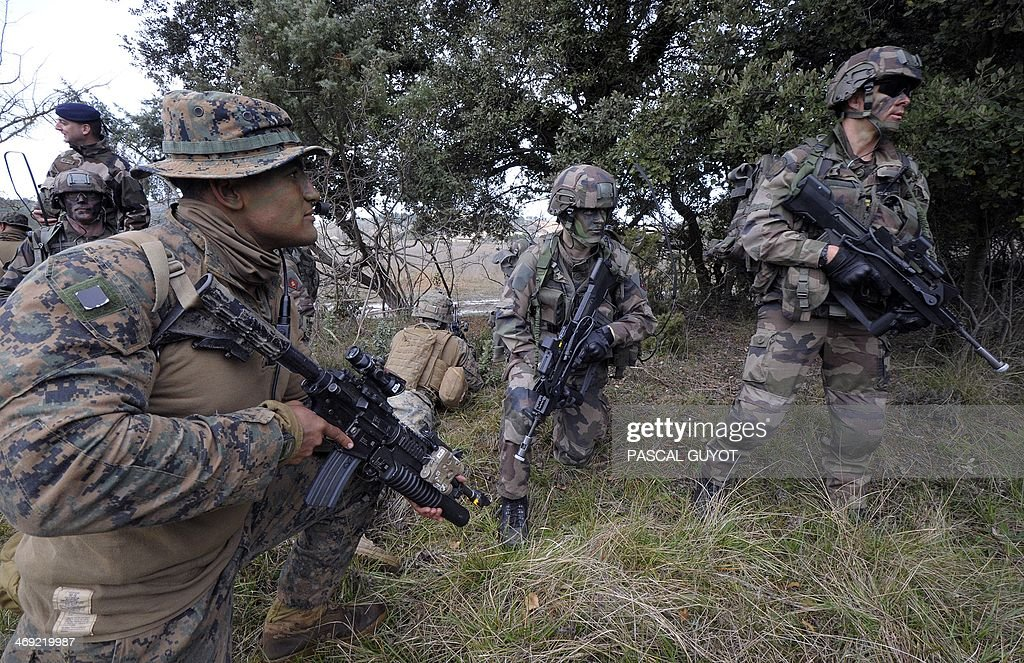 Soldiers (L) of the US Special Purpose Marine Air Ground Task Force for Crisis Response, (SPMAGTF-CR), and soldiers (R) of the French 21st Marine Infantry Regiment (RIMa) take part in a Franco-American military exercise called 'Garrigues Fury 2014' on February 13, 2014 at military camp of Garrigues, near Nimes, southern France. The SPMAGTF-CR, was created after the armed attack against the U.S. consulate in Benghazi, Libya, in September 2012, in which four people, including the U.S. ambassador, perished. The mission of SPMAGTF-CR is to intervene rapidly in Africa. The objective of the exercise is to share the techniques and methods of action used in urban warfare. A Bell Boeing V-22 Osprey, an American multi-mission, military, tiltrotor aircraft, is seen above them.
