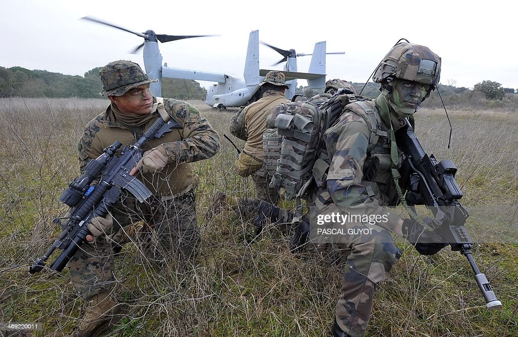 Soldiers (L) of the US Special Purpose Marine Air Ground Task Force for Crisis Response, (SPMAGTF-CR), and soldiers (R) of the French 21st Marine Infantry Regiment (RIMa) take part in a Franco-American military exercise called 'Garrigues Fury 2014' on February 13, 2014 at military camp of Garrigues, near Nimes, southern France. The SPMAGTF-CR, was created after the armed attack against the U.S. consulate in Benghazi, Libya, in September 2012, in which four people, including the U.S. ambassador, perished. The mission of SPMAGTF-CR is to intervene rapidly in Africa. The objective of the exercise is to share the techniques and methods of action used in urban warfare.