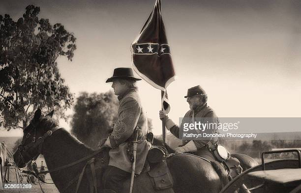 Soldiers on horseback ride into camp in uniforms carrying confederate flag Civil War reenactment held at a park in Los Angeles California Black and...