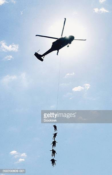 Soldiers on rope hanging from Sikorsky UH-60 Blackhawk, low angle view