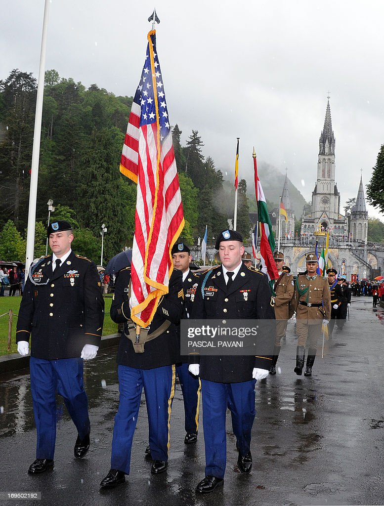 US soldiers parade in front the Basilica of our Lady of the Rosary in the French southwestern pilgrimage city of Lourdes on the day of the opening parade of the 55th International Military Pilgrimage, on May 25, 2013. The city of Lourdes welcomed over 12,000 soldiers and their families from 35 countries during the pilgrimage, which runs from May 24 to 26.
