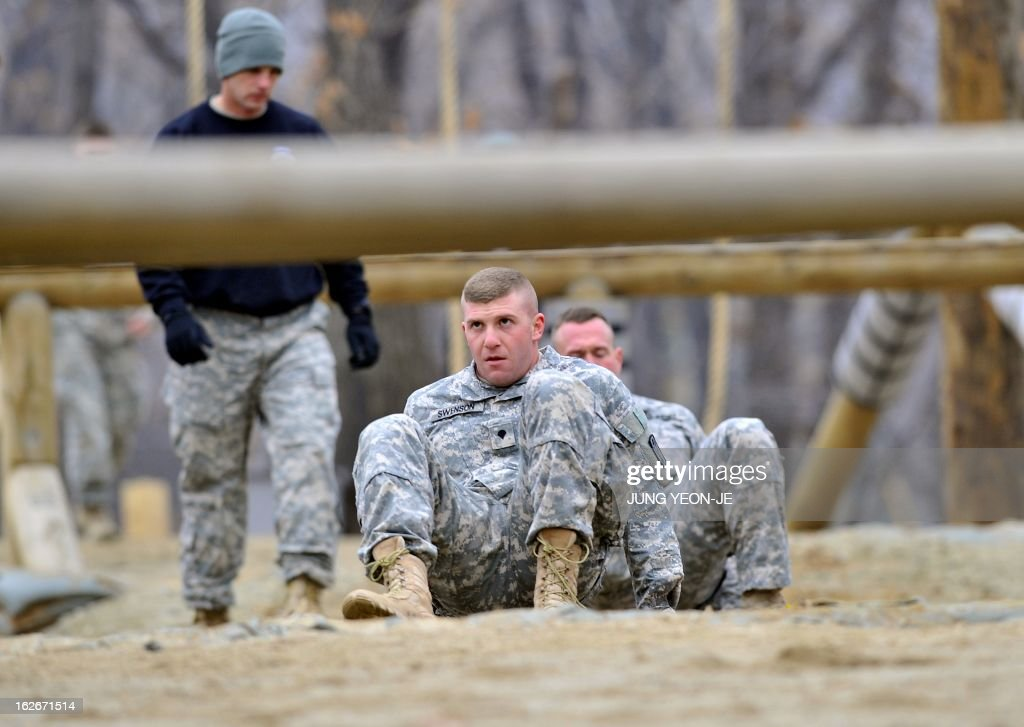 US soldiers pass an obstacle during an Air Assault training course at a US Army base in Dongducheon, 40 kms north of Seoul, on February 26, 2013. About 250 US soldiers from the 2nd Infantry Division located in South Korea took part in the two-week course until March 8, focused on combat assault operations involving US Army rotary-wing aircraft.