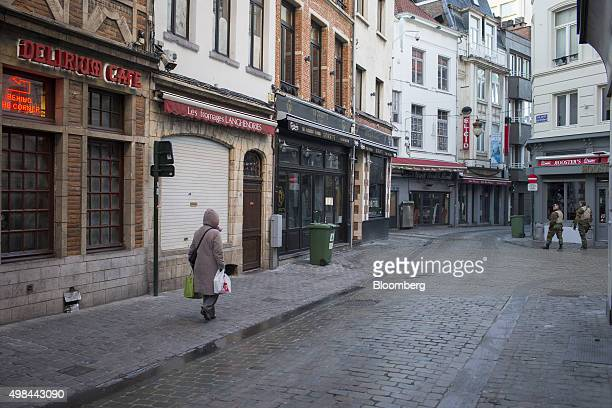 Soldiers pass bars as they patrol the streets in Brussels Belgium on Monday Nov 23 2015 The search for a key suspect in the Paris terror attacks kept...