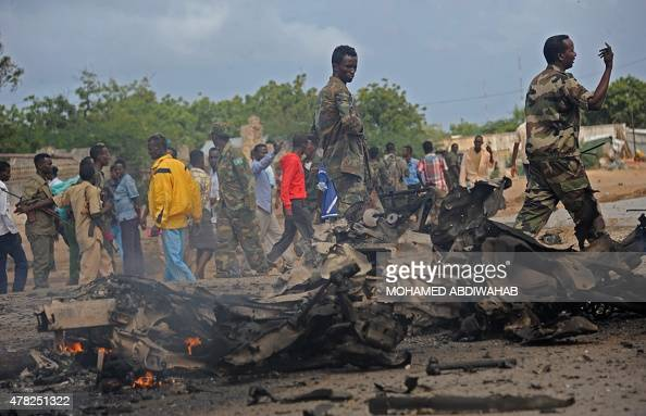 Soldiers patrol around the wreckage of a suicide car bomber that smashed into pickup truck carrying security officers on June 24 2015 in Mogadishu in...