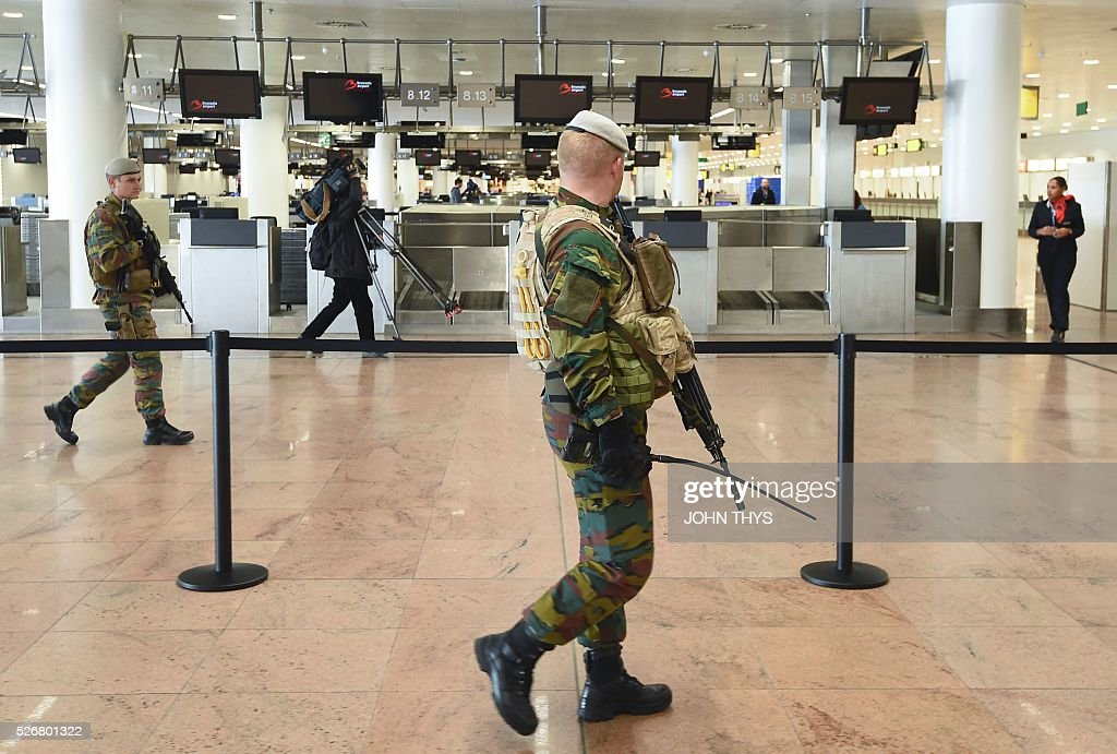 Soldiers patrol during the partial reopening of the departure hall of Brussels Airport in Zaventem on May 1, 2016, after it was badly damaged in twin suicide attacks on March 22, that killed 16 people. A total of 32 people were killed and more than 300 wounded in coordinated suicide bombings at the airport and a metro station in central Brussels on March 22 in Belgium's worst ever terror attacks. / AFP / JOHN