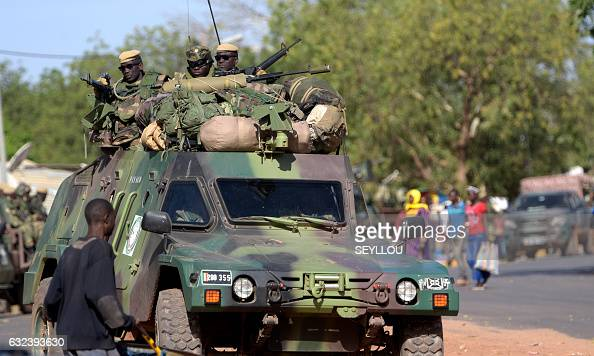 soldiers patrol in an armoured vehicle in front of the Second Battalion Camp in Farafegny on January 22 2017 West African troops approached the...