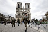 Soldiers patrol in front of the Notre Dame Cathedral on November 16 2015 in Paris ahead of a minutes silence for victims of the attacks claimed by...