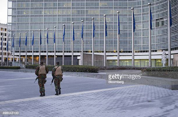 Soldiers patrol outside the European Council building as European Union flags hang in Brussels Belgium on Monday Nov 23 2015 The search for a key...
