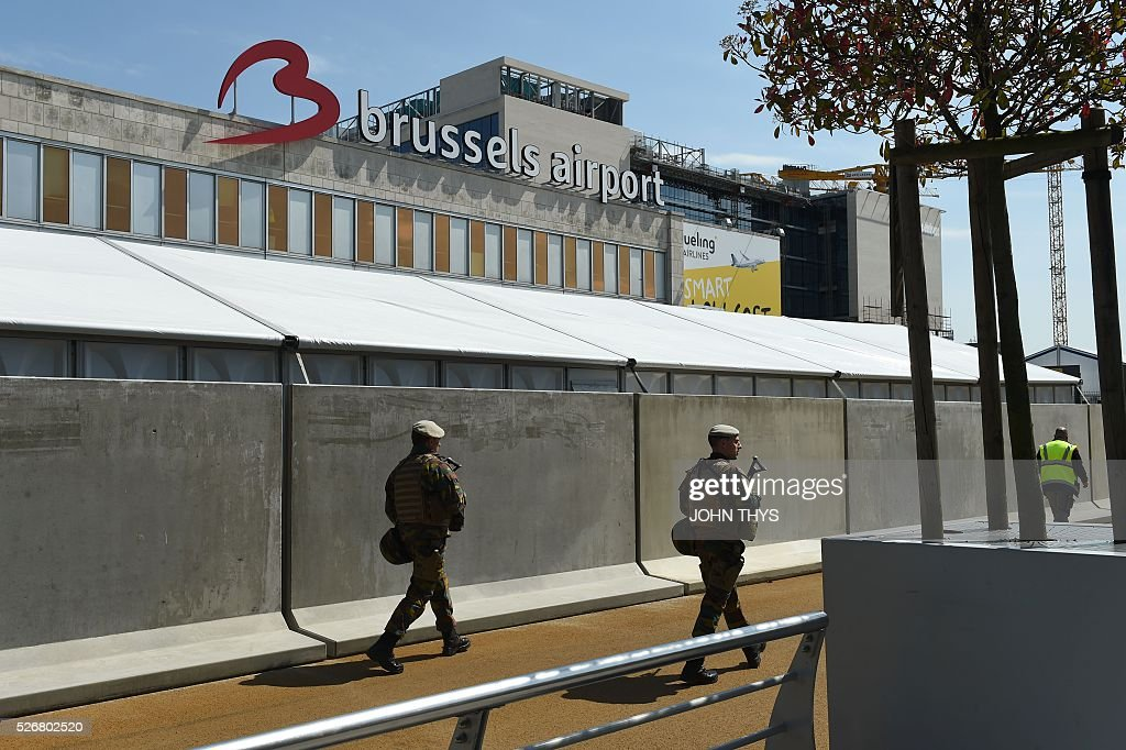 Soldiers patrol outside Zaventem Airport in Brussels on May 1, 2016, during the partial reopening of the departure hall after it was badly damaged in twin suicide attacks on March 22, that killed 16 people. A total of 32 people were killed and more than 300 wounded in coordinated suicide bombings at the airport and a metro station in central Brussels on March 22 in Belgium's worst ever terror attacks. / AFP / JOHN