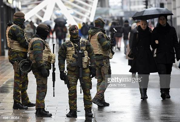 Soldiers patrol the Rue Neuve pedestrian shopping street in Brussels on November 21 2015 All metro train stations in Brussels will be closed on...
