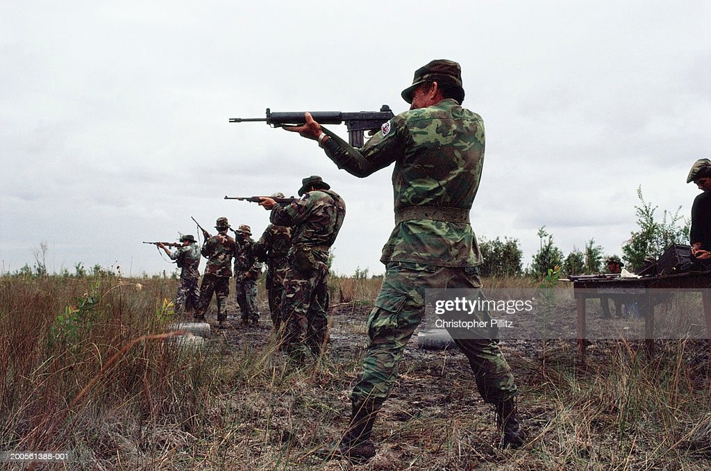 Soldiers pointing with guns in field, side view