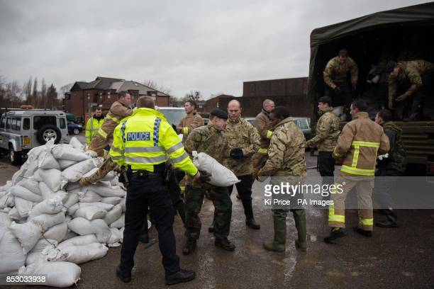 Soldiers police and firefighters load up sandbags onto a lorry in Datchet Berkshire to help to defend the town from the floods that have brought...
