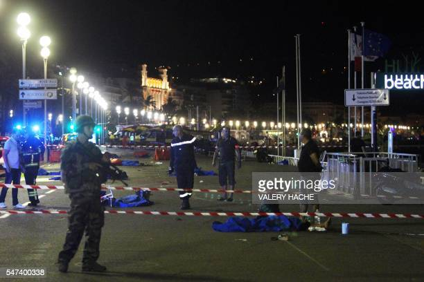 Soldiers police officers and firefighters walk near dead bodies covered with a blue sheets on the Promenade des Anglais seafront in the French...