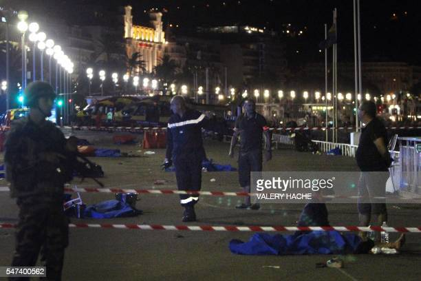 TOPSHOT Soldiers police officers and firefighters walk near dead bodies covered with a blue sheets on the Promenade des Anglais seafront in the...