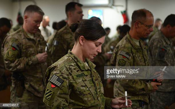 US soldiers pray as they attend a religious ceremony on Christmas Eve at a US military base in Kabul on December 24 2013 There are presently around...