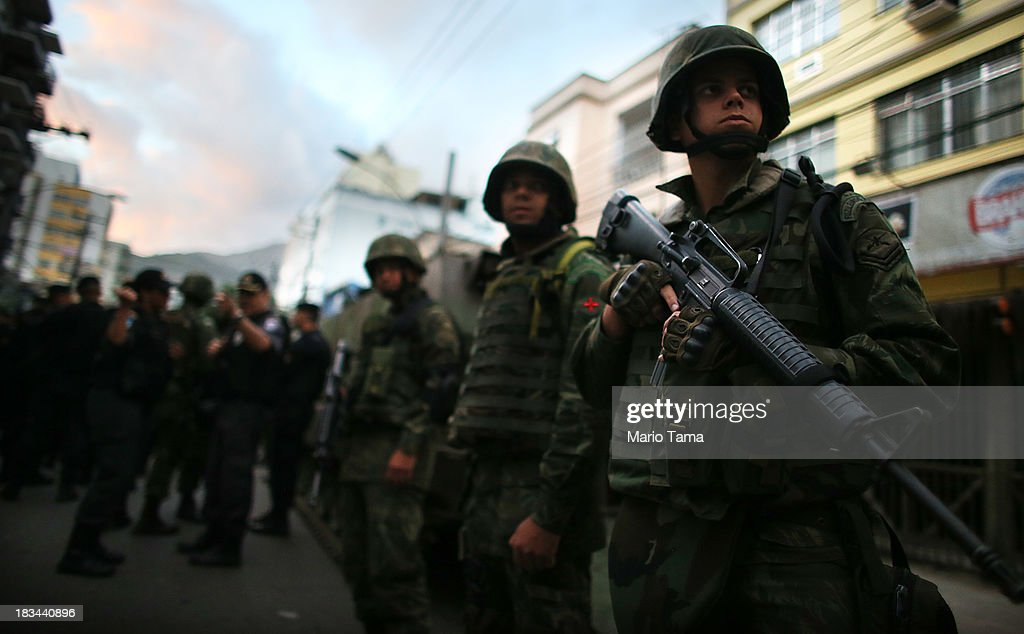 Soldiers prepare for a 'pacification' operation in the nearby favela complex of Lins de Vasconcelos, in the North Zone, on October 6, 2013 in Rio de Janeiro, Brazil. The favela complex, or shanty town, was previously controlled by drug traffickers and will now be occupied by the city's 35th UPP or 'Police Pacification Unit'. The favela pacifications are occurring amid Rio de Janeiro's efforts to improve security ahead of the 2014 FIFA World Cup and 2016 Olympic Games.