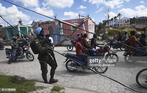 UN soldiers provide security for trucks from the UN's World Foof Programme in Port Salut southwest of PortauPrince on October 12 following the...