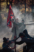 Soldiers raising confederate flag during Civil war reenactment